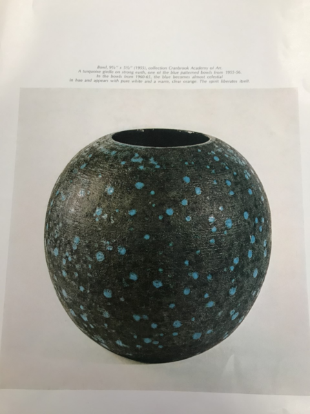 Image of a round black vase with blue spotted design with descriptive text
