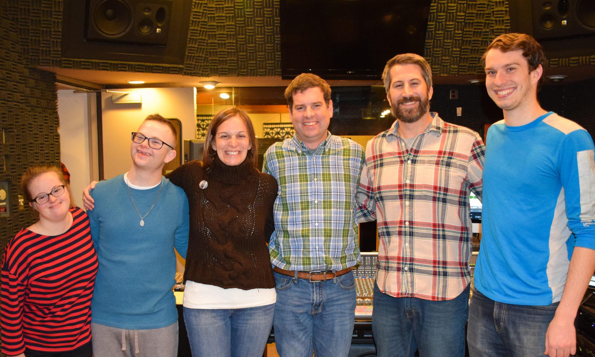 several people standing shoulder to shoulder smiling in studio