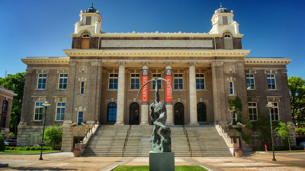 Exterior view of Carnegie Library with blue sky and statue