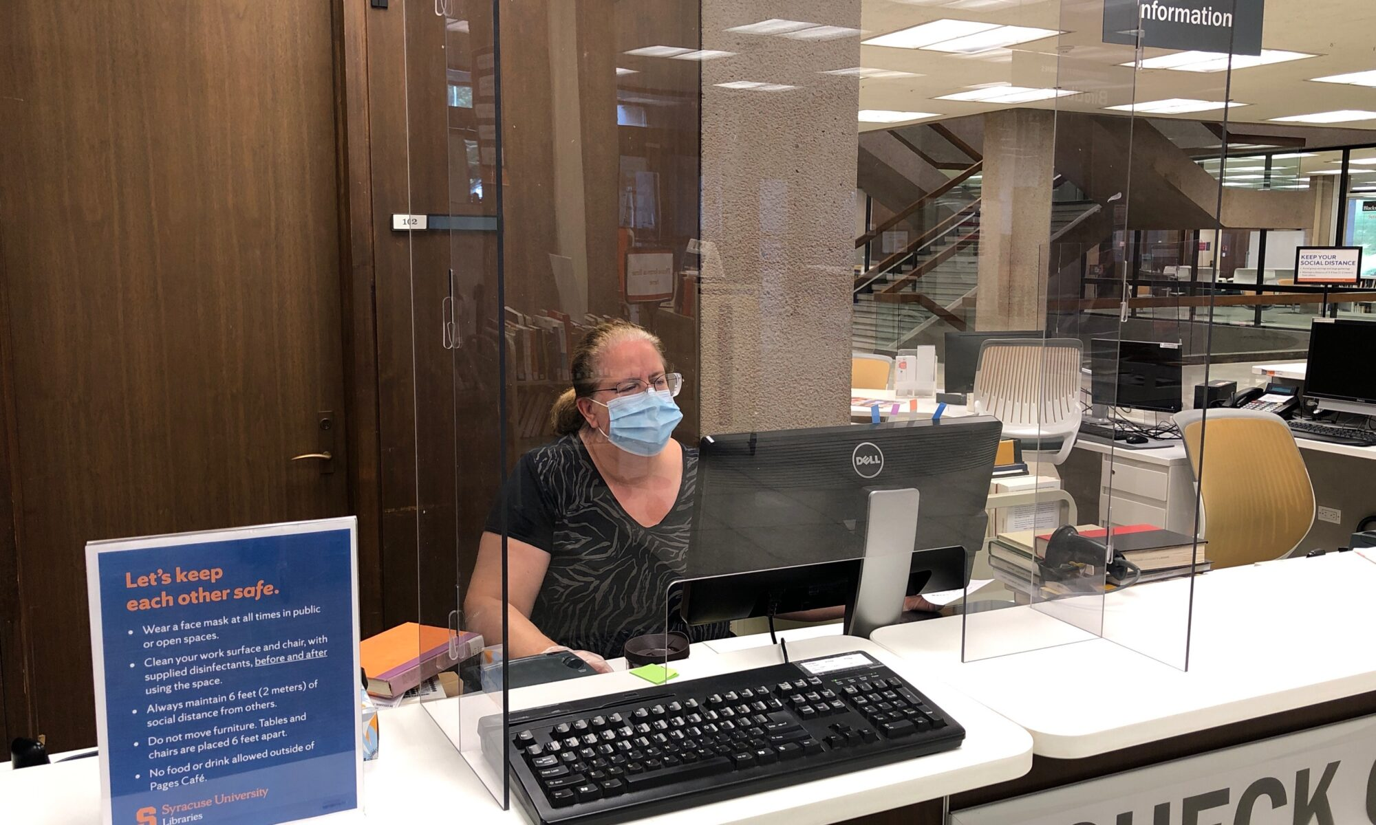 person with face mask sitting behind plexiglass check out desk at library