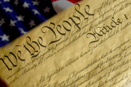 upper right corner of U.S. Constitution document with American flag in background