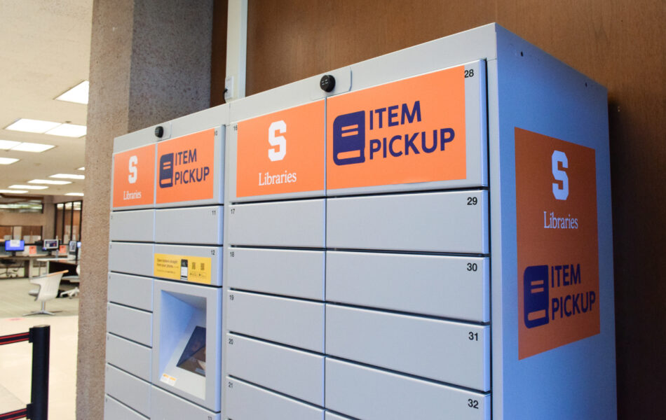 Gray metal Item Pickup lockers with orange Libraries logo and Item Pickup stickers in Bird Library