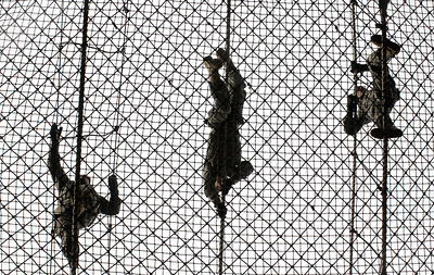 silhouette of three people doing military drill climbing up rope