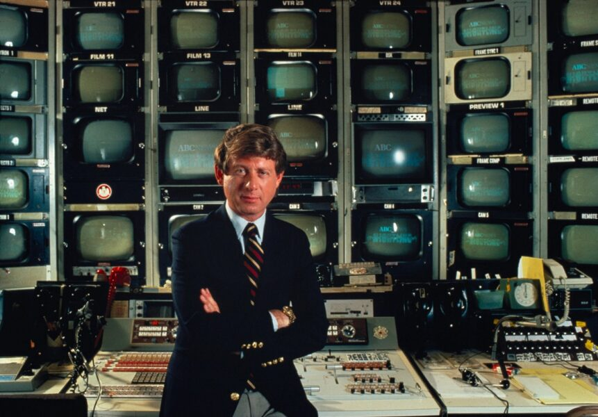 ABC News anchor Ted Koppel posed in front of news production room with rows and columns of tv screens