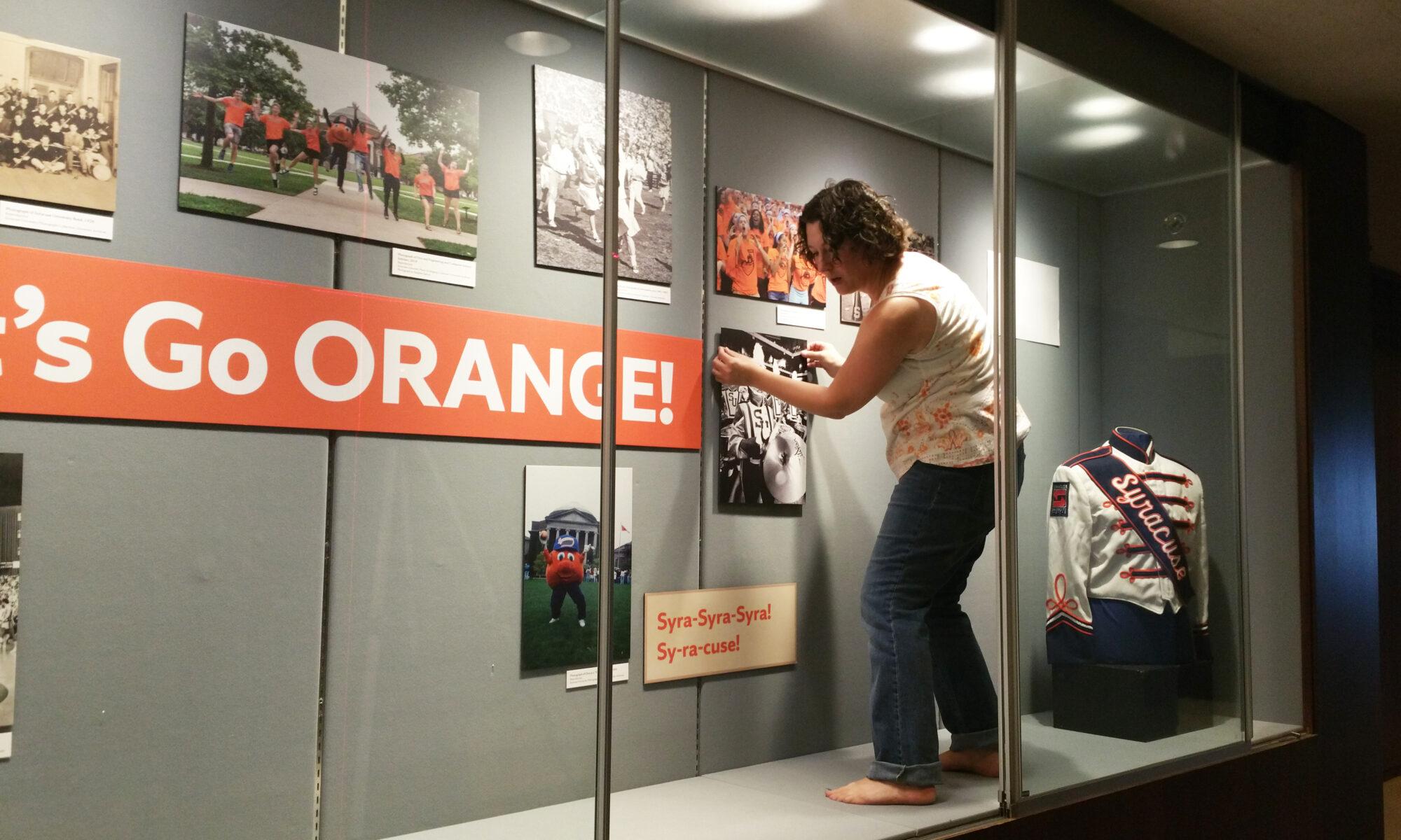 Meg Mason standing inside a display case to install pieces of Syracuse University memorabilia